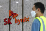 A man passes by the logo of SK Hynix Inc. at its office in Seongnam, South Korea, Tuesday, Oct. 20, 2020. Intel has agreed to a $9 billion deal to sell most of its memory business to South Korea's SK Hynix as it moves toward more diverse technologies while shedding a major Chinese factory at a time of deepening trade friction between Washington and Beijing. (AP Photo/Ahn Young-joon)