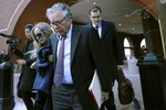 Insys Therapeutics founder John Kapoor, front, departs federal court Thursday, Jan. 23, 2020, in Boston, after he was sentenced to 5 1/2 years in prison for orchestrating a bribery and kickback scheme prosecutors said helped fuel the opioid crisis. He was found guilty the previous May of racketeering and conspiracy in a scheme where millions of dollars in bribes were paid to doctors across the United States to prescribe the company's highly addictive oral fentanyl spray, known as Subsys. (AP Photo/Charles Krupa)
