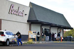 In this Thursday, June 25, 2020 photo provided by C.M. Clay, shoppers wait in line outside a grocery store in Whiteriver, Ariz., on the Fort Apache Indian Reservation. The reservation, home to the White Mountain Apache Tribe, will be under lockdown this weekend to help slow the spread of the coronavirus. (C.M. Clay/White Mountain Apache Tribe via AP)
