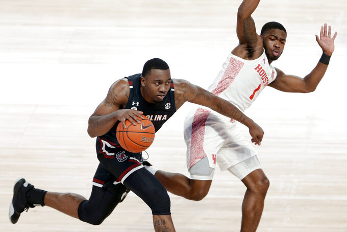 South Carolina guard Jermaine Couisnard, left, pushes off Houston guard Jamal Shead (1) as he drives to the basket during the second half of an NCAA college basketball game Saturday, Dec. 5, 2020, in Houston. (AP Photo/Michael Wyke)