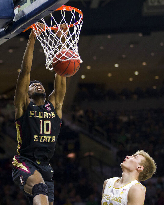 Florida State's Malik Osborne (10) dunks next to Notre Dame's Dane Goodwin during the first half of an NCAA college basketball game Wednesday, March 4, 2020, in South Bend, Ind. (AP Photo/Robert Franklin)