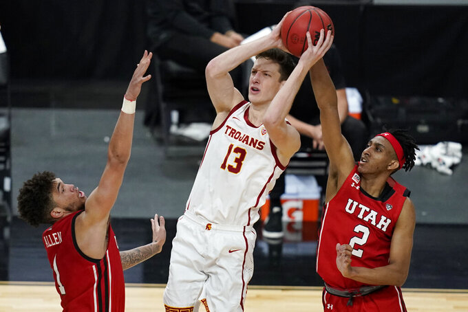 Southern California's Drew Peterson (13) shoots over Utah's Timmy Allen, left, and Ian Martinez (2) during the second half of an NCAA college basketball game in the quarterfinal round of the Pac-12 men's tournament Thursday, March 11, 2021, in Las Vegas. (AP Photo/John Locher)