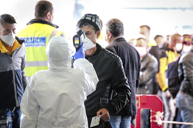 An airport employee checks the temperature of a Romanian seasonal worker outside the Avram Iancu international airport, in Cluj, central Romania, Thursday, April 9, 2020. More then 1800 workers from across Romania are traveling on 12 flights to Berlin, Baden Bade and Dusseldorf in Germany, most of them to work in asparagus farms.(AP Photo/Raul Stef)