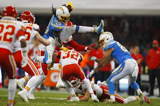 Los Angeles Chargers running back Melvin Gordon leaps over Kansas City Chiefs strong safety Tyrann Mathieu during the first half of an NFL football game Monday, Nov. 18, 2019, in Mexico City. (AP Photo/Eduardo Verdugo)