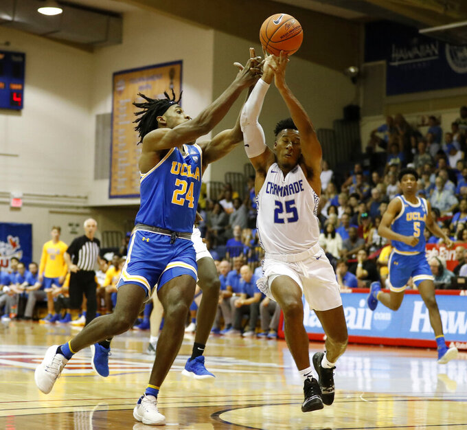 UCLA forward Jalen Hill (24) and Chaminade guard Kendall Small (25) fight for a loose ball during the first half of an NCAA college basketball game Tuesday, Nov. 26, 2019, in Lahaina, Hawaii. (AP Photo/Marco Garcia)