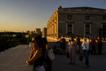 """People watch the sunset at the Royal Palace in Madrid, Spain, Thursday, July 8, 2021. Spain's top diplomat is pushing back against French cautions over vacationing on the Iberian peninsula. Southern Europe's holiday hotspots worry that repeated changes to rules on who can visit is putting people off travel. On Thursday, France's secretary of state for European affairs, Clement Beaune, advised people to """"avoid Spain and Portugal as destinations"""" when booking their holidays because COVID-19 infections are surging there. (AP Photo/Manu Fernandez)"""