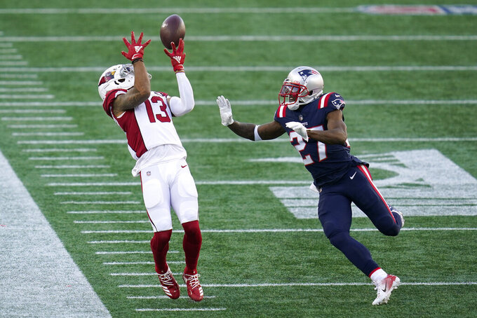 Arizona Cardinals wide receiver Christian Kirk reaches for a pass as New England Patriots defensive back J.C. Jackson, right, defends in the first half of an NFL football game, Sunday, Nov. 29, 2020, in Foxborough, Mass. (AP Photo/Charles Krupa)