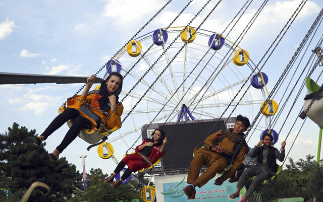 Visitors enjoy a ride at Kabul City Park in Kabul, Afghanistan, Friday, July 24, 2020. Desperate for relief from endless war combined with the pandemic, Afghans are rushing back to public recreation as the government eases the lockdown it imposed to fight coronavirus. Since mid-July, Afghans can once again frequent parks, swimming pools and gyms, shop in malls and celebrate marriages in wedding halls. (AP Photo/Rahmat Gul)