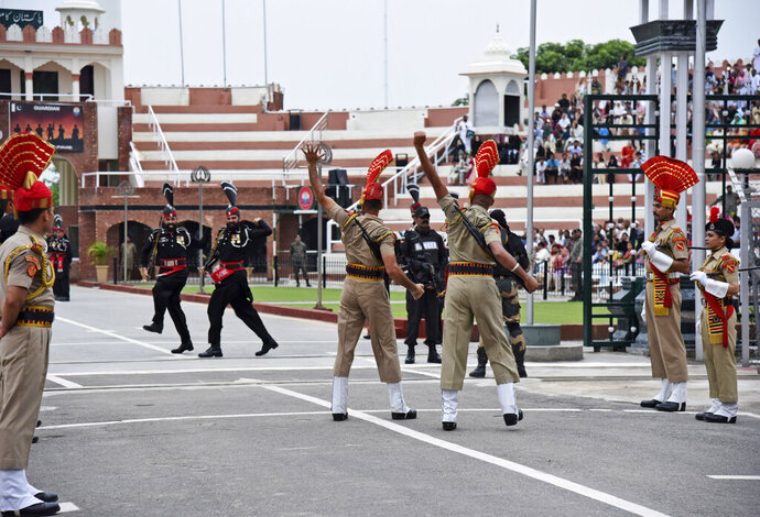 Pakistan Rangers soldiers, in black, face Indian Border Security Force soldiers at a daily closing ceremony on the Indian side of the Attari-Wagah border, Friday, Aug. 9, 2019. About 8,000 supporters of a Pakistani Islamist party are marching toward the Indian embassy in Islamabad to denounce New Delhi's actions to change the special status of the disputed Himalayan region of Kashmir. Both Pakistan and India claim all of Kashmir. Tensions have soared this week after India downgraded the Muslim-majority region's status from statehood to a territory. (AP Photo/Prabhjot Gill)