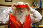Brad Six adjusts his protective face shield as he prepares to work as Santa Claus at Bass Pro Shops, Friday, Nov. 20, 2020, in Miami. This is Santa Claus in the Coronavirus Age, where visits are done with layers of protection or moved online. Putting hundreds of kids a day onto your lap to talk directly into your face — that's not happening. (AP Photo/Lynne Sladky)