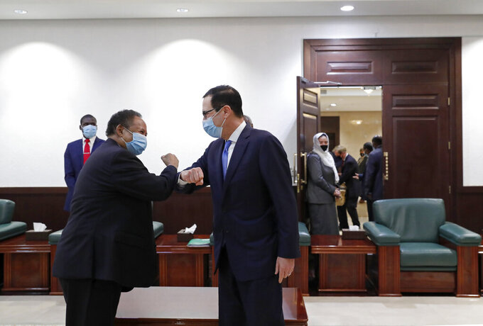 CORRECTS NAME TO STEVEN MNUCHIN ADDS DETAILS - Sudanese Prime Minister Abdullah Hamdok, left, elbow bumps as he welcomes US Treasury Secretary Steven Mnuchin to the Cabinet Building, in Khartoum, Sudan, Wednesday, Jan. 6, 2021. The U.S. and Sudan have agreed to settle the African country's debt to the World Bank. The move comes after Mnuchin arrived in Sudan, the first visit by a senior American official since President Donald trump removed Sudan from the list of state sponsors of terrorism. (AP Photo)