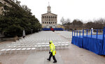 A man walks across War Memorial Plaza near the Tennessee State Capitol Friday, Jan. 18, 2019, in Nashville, Tenn., where preparations have been made for the inauguration of Tennessee Gov.-elect Bill Lee on Saturday. Lee's inauguration is being moved indoors to the War Memorial Auditorium because of forecasts for weekend rain and thunderstorms. (AP Photo/Mark Humphrey)