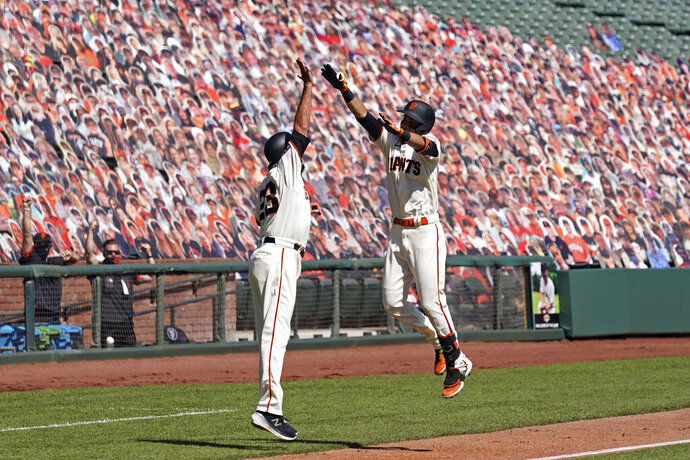 San Francisco Giants' Mauricio Dubon, right, is greeted by third base coach Ron Wotus after hitting a home run off San Diego Padres starting pitcher Adrian Morejon in the second inning of a baseball game Sunday, Sept. 27, 2020, in San Francisco. (AP Photo/Eric Risberg)