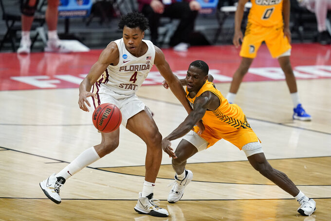 Florida State's Scottie Barnes (4) is defended by UNC-Greensboro's Isaiah Miller (1) during the second half of a first-round game in the NCAA men's college basketball tournament at Banker's Life Fieldhouse, Saturday, March 20, 2021, in Indianapolis. Florida State defeated UNC-Greensboro 64-54. (AP Photo/Darron Cummings)