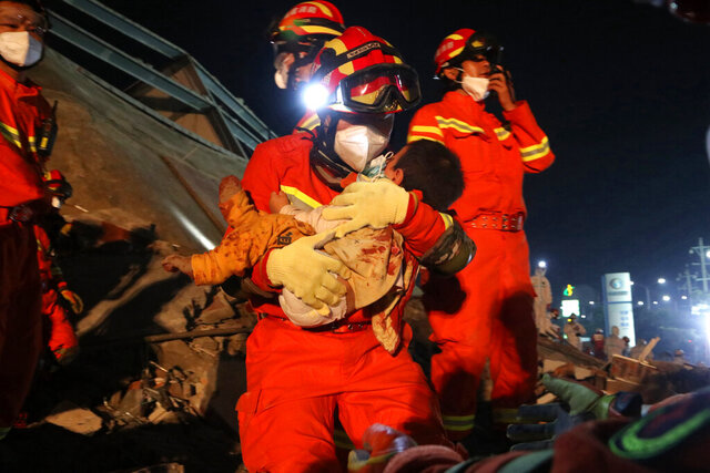 In this March 8, 2020, photo, rescuers pull a young child out from the rubbles of a collapsed hotel on a stretcher in Quanzhou, southeast China's Fujian Province. Several have been killed and others trapped when in the collapsed Chinese hotel that was being used to isolate people who had arrived from other parts of China hit hard by the coronavirus outbreak, authorities said Sunday. (Chinatopix Via AP)