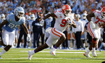 Clemson's Travis Etienne (9) evades North Carolina Tar Heels's Storm Duck (29) as he runs for a touchdown during the second quarter of an NCAA college football game in Chapel Hill, N.C., Saturday, Sept. 28, 2019. (AP Photo/Chris Seward)