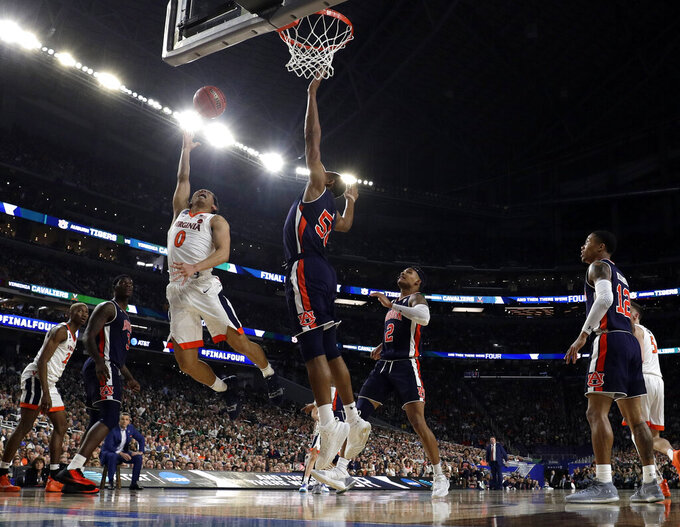 Virginia's Kihei Clark (0) takes a shot against Auburn's Austin Wiley (50) during the second half in the semifinals of the Final Four NCAA college basketball tournament, Saturday, April 6, 2019, in Minneapolis. (AP Photo/David J. Phillip)
