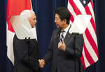 U.S. Vice President Mike Pence, left, and Japanese Prime Minister Shinzo Abe shake hands after they read a joint statement at Abe's official residence in Tokyo Tuesday, Nov. 13, 2018. (AP Photo/Eugene Hoshiko)