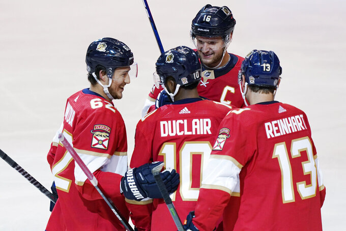 Florida Panthers teammates congratulate left wing Anthony Duclair (10) after he scored a goal during the second period at an NHL preseason second doubleheader hockey game against the Nashville Predators, Sunday, Sept. 26, 2021, in Sunrise, Fla. (AP Photo/Marta Lavandier)