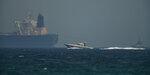 An Emirati coast guard vessel passes an oil tanker off the coast of Fujairah, United Arab Emirates, Monday, May 13, 2019. Saudi Arabia said Monday two of its oil tankers were sabotaged off the coast of the United Arab Emirates near Fujairah in attacks that caused