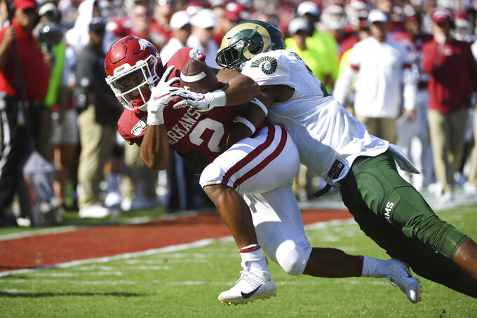 Arkansas running back Chase Hayden makes a catch in front of a Colorado State defender Tron Folsom during the first half of an NCAA college football game, Saturday, Sept. 14, 2019 in Fayetteville, Ark. (AP Photo/Michael Woods)