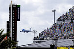 Fans watch from the grandstands as Air Force One circles the Daytona International Speedway as President Donald Trump makes his arrival to attend the NASCAR Daytona 500 auto race at Daytona International Speedway, Sunday, Feb. 16, 2020, in Daytona Beach, Fla. (AP Photo/Terry Renna)