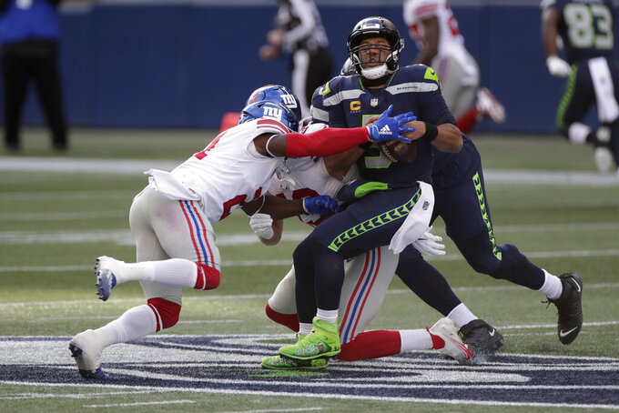Seattle Seahawks quarterback Russell Wilson is sacked by New York Giants safety Jabrill Peppers, left, during the first half of an NFL football game, Sunday, Dec. 6, 2020, in Seattle. (AP Photo/Larry Maurer)