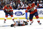 Calgary Flames' Curtis Lazar (20) falls to the ice as he goes for the puck against Florida Panthers' Micheal Haleym, right, during the first period of an NHL hockey game Friday, Jan. 12, 2018, in Sunrise, Fla. (AP Photo/Lynne Sladky)
