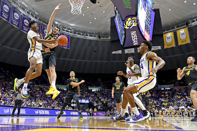 LSU guard Javonte Smart, left, makes the outlet pass while driving to the basket as Missouri forward Reed Nikko (14) defends in the first half of an NCAA college basketball game, Tuesday, Feb. 11, 2020, in Baton Rouge, La. (AP Photo/Bill Feig)