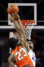 Kansas State's Xavier Sneed, back, blocks a shot by Florida A&M's Bryce Moragne (23) during the first half of an NCAA college basketball game Monday, Dec. 2, 2019, in Manhattan, Kan. (AP Photo/Charlie Riedel)