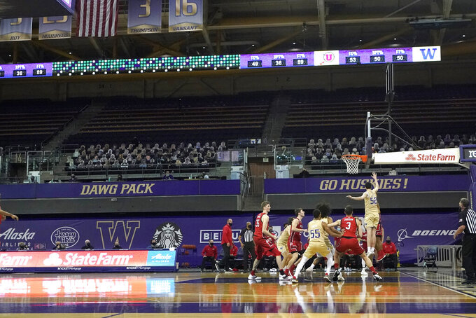 Washington plays Utah during the second half of an NCAA college basketball game, Sunday, Jan. 24, 2021, before empty seats in Hec Edmundson Pavilion in Seattle. Due to the COVID-19 pandemic, fans were not allowed to watch the game in person. (AP Photo/Ted S. Warren)