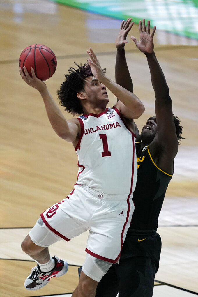 Oklahoma forward Jalen Hill (1) shoots over Missouri forward Kobe Brown, right, during the first half of a first-round game in the NCAA men's college basketball tournament at Lucas Oil Stadium, Saturday, March 20, 2021, in Indianapolis. (AP Photo/Darron Cummings)