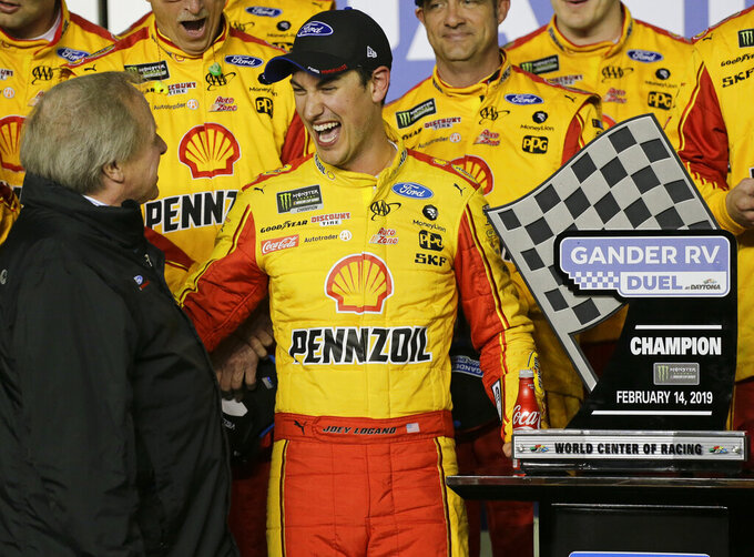 Edsel Ford II, left, congratulates Joey Logano, center, who had won the second of two qualifying auto races for the NASCAR Daytona 500 at Daytona International Speedway, Thursday, Feb. 14, 2019, in Daytona Beach, Fla. (AP Photo/Terry Renna)