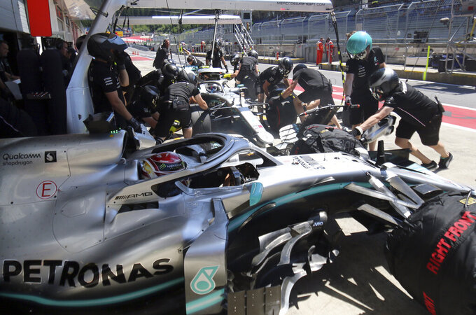 Mercedes driver Lewis Hamilton of Britain, in the foreground, sits in his car as mechanics work on the car of teammate Valtteri Bottas of Finland, in the background, during the first free practice session for the Austrian Formula One Grand Prix at the Red Bull Ring racetrack in Spielberg, southern Austria, Friday, June 28, 2019. The race will be held on Sunday. (AP Photo/Ronald Zak)