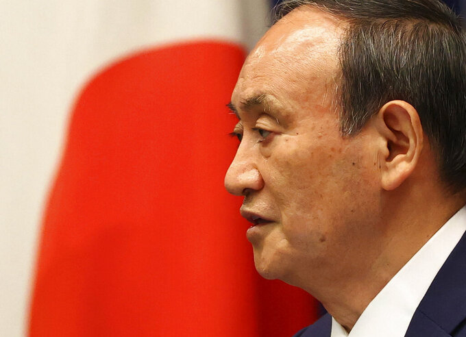 Japan's Prime Minister Yoshihide Suga attends a news conference on Japan's response to the coronavirus pandemic at his official residence during the Tokyo 2020 Olympic Games in Tokyo, Japan, Friday, July 30, 2021. Suga expanded a coronavirus state of emergency to four more areas in addition to Tokyo on Friday following record spikes in infections as the capital hosts the Olympics. (Issei Kato/Pool Photo via AP)