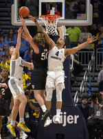 Butler's Joey Brunk, center, is defended by Marquette's Sam Hauser, left, and Theo John, right, during the first half of an NCAA college basketball game Wednesday, Feb. 20, 2019, in Milwaukee. (AP Photo/Darren Hauck)