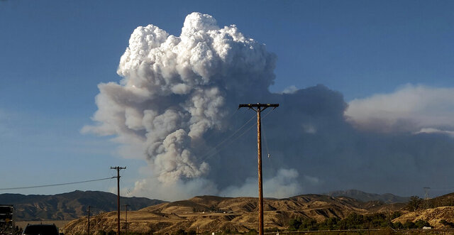 The Lake Hughes fire sends a plume of smoke over Angeles National Forest on Wednesday, Aug. 12, 2020, in a view from Santa Clarita, Calif. (AP Photo/Ringo H.W. Chiu)