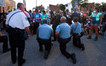 Police officers from Ferguson, Mo., join protesters to remember George Floyd by taking a knee in the parking lot of the police station on Saturday, May 30, 2020. The demonstration was prompted by the death of Floyd, a black man who was killed in police custody in Minneapolis on May 25. (Robert Cohen/St. Louis Post-Dispatch via AP)