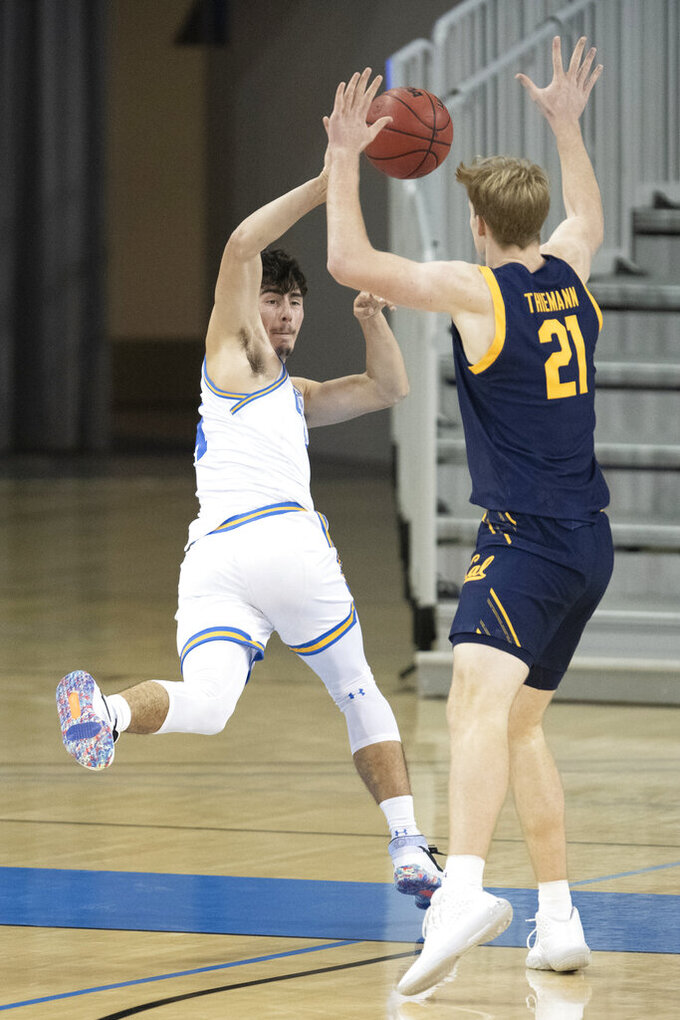 UCLA guard Jaime Jaquez Jr., left, saves the ball from going out of bounds as California forward Lars Thiemann defends during the first half of an NCAA college basketball game Sunday, Dec. 6, 2020, in Los Angeles. (AP Photo/Kyusung Gong)