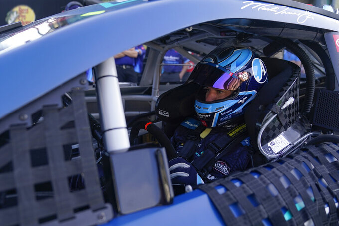 Martin Truex Jr. sits in his car before qualifications for the NASCAR Series auto race at Indianapolis Motor Speedway, Sunday, Aug. 15, 2021, in Indianapolis. (AP Photo/Darron Cummings)