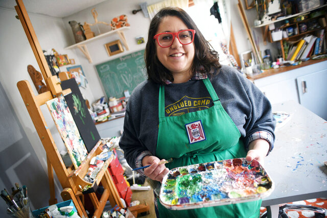 In this March 25, 2020 photo, artist Nicole Gagner poses in Bismarck, N.D. To adapt to the coronavirus outbreak, Gagner is teaching online workshops with artists from across the country. (Mike McClearyThe Bismarck Tribune via AP)