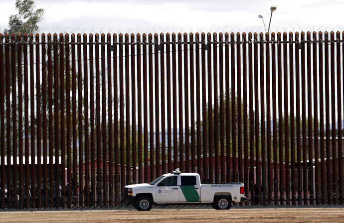 FILE - In this April 5, 2019, file photo, a U.S. Customs and Border Protection vehicle sits near the wall as President Donald Trump visits a new section of the border wall with Mexico in El Centro, Calif. A new report by a federal watchdog says the U.S. Customs and Border Protection agency misspent millions of dollars meant for migrant care during the 2019 surge in border crossings. The report by the U.S. Government Accountability Office was released Thursday, June 10, 2020. (AP Photo/Jacquelyn Martin, File)