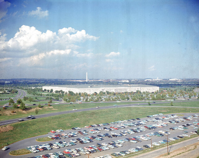 """File-This undated file photo shows the Pentagon, headquarters of the U.S. Department of Defense, with the Washington Monument in background and a large parking lot in foreground, in Arlington, Va.  The Pentagon is proposing to end an arrangement in which a single military officer leads two of the nation's main cybersecurity organizations, a move that a leading Democrat said Saturday, Dec. 19, 2020, makes him """"profoundly concerned"""" amid a large-scale cyberattack on U.S. government computer systems.  (AP Photo, File)"""