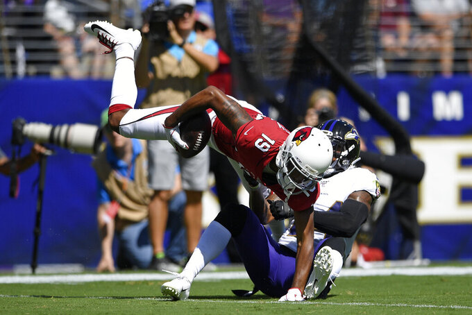 Arizona Cardinals wide receiver KeeSean Johnson, left, tries to break free from Baltimore Ravens cornerback Brandon Carr after making a catch in the first half of an NFL football game, Sunday, Sept. 15, 2019, in Baltimore. (AP Photo/Nick Wass)