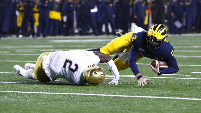 Notre Dame linebacker Jordan Genmark Heath (2) tackles Michigan quarterback Shea Patterson (2) in the second half of an NCAA college football game in Ann Arbor, Mich., Saturday, Oct. 26, 2019. (AP Photo/Paul Sancya)