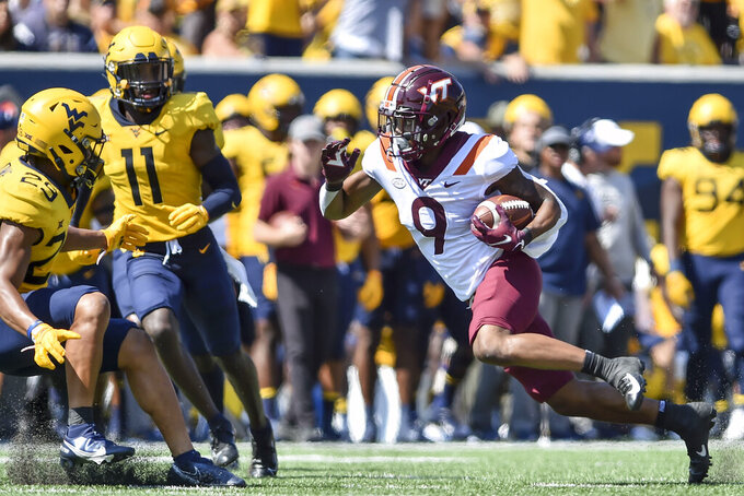Virginia Tech wide receiver Tayvion Robinson (9) picks yardage after a catch against West Virginia during the first half of an NCAA college football game in Morgantown, W.Va., Saturday, Sep. 18, 2021. (AP Photo/William Wotring)