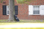 A U.S. Marshals' shield leans against a tree outside an apartment complex at the scene of a shooting, Wednesday, Feb. 12, 2020, in Baltimore. Two law enforcement officers with a fugitive task force were injured and a suspect died in the shooting, the U.S. Marshals Service said. (Ulysses Muñoz/The Baltimore Sun via AP)