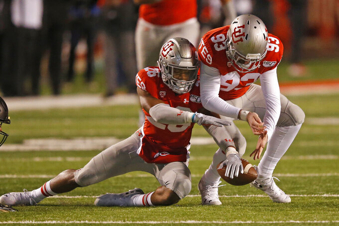 Utah's Terrell Burgess (26) and Semisi Lauaki (93) reach for a fumble against Colorado in the first half during an NCAA college football game Saturday, Nov. 30, 2019, in Salt Lake City. (AP Photo/Rick Bowmer)