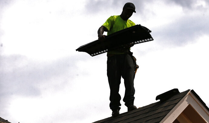 In this June 19, 2019, photo Larry McGee balances along a roof edge as he carries roof over ridge vent that he and others will be laying down on a new house in a Brandon, Miss., neighborhood. On Wednesday, July 17, the Commerce Department reports on U.S. home construction in June. (AP Photo/Rogelio V. Solis)