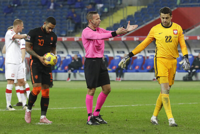 Referee Orel Grinfeld of Israel tells Poland's goalkeeper Lukasz Fabianski to go to his goal as Netherlands' Memphis Depay, left, prepares to take a penalty shot during the Nations League soccer match between Poland and The Netherlands at Silesian Stadium in Chorzow, Poland, Wednesday, Nov. 18, 2020. (AP Photo/Czarek Sokolowski)